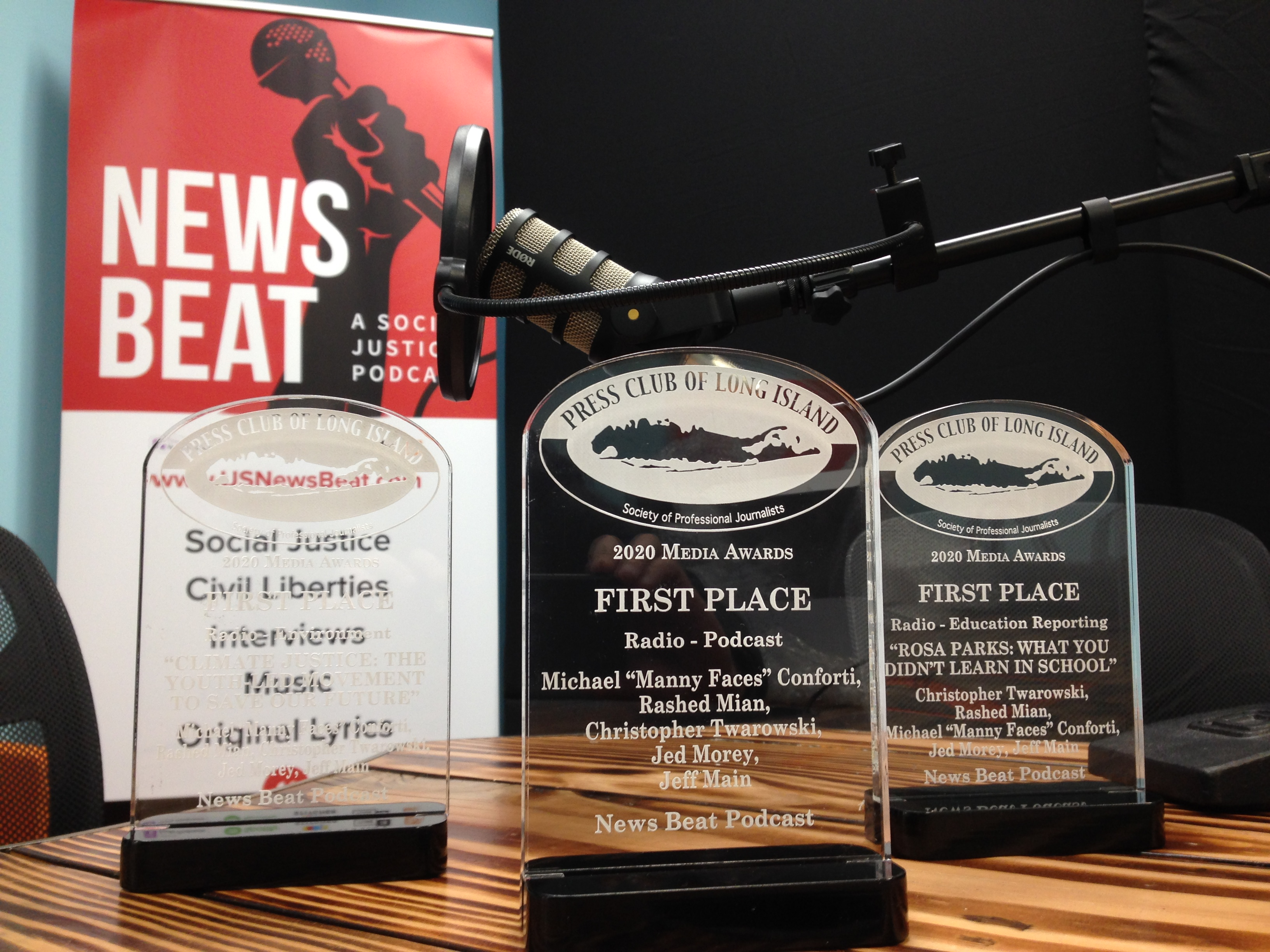 Image of three First Place awards for News Beat podcast in front of a microphone and logo banner