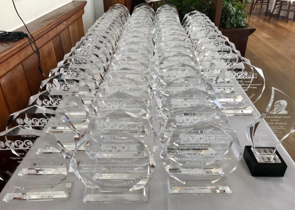 Dozens of Crystal New York Press Club Journalism Awards Arranged Across a Table