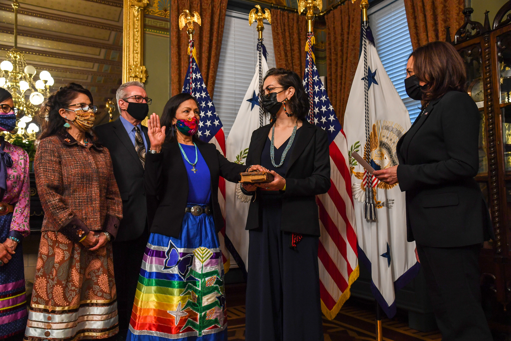 Interior Secretary Deb Haaland is being swrong in to her new position. She has a hand raised and is facing Vice President Kamala Harris.
