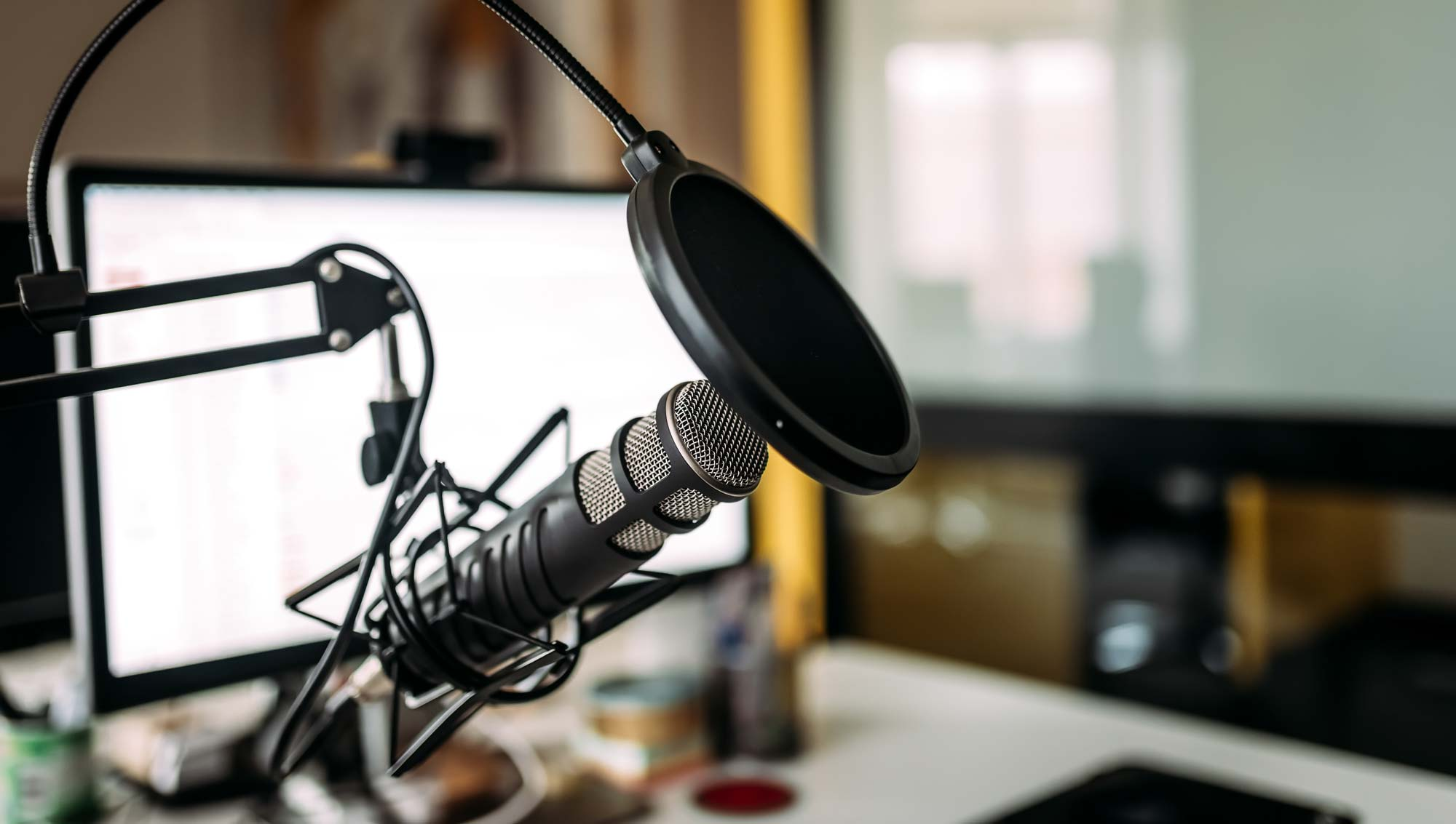 Image of a podcast mic in front of computer